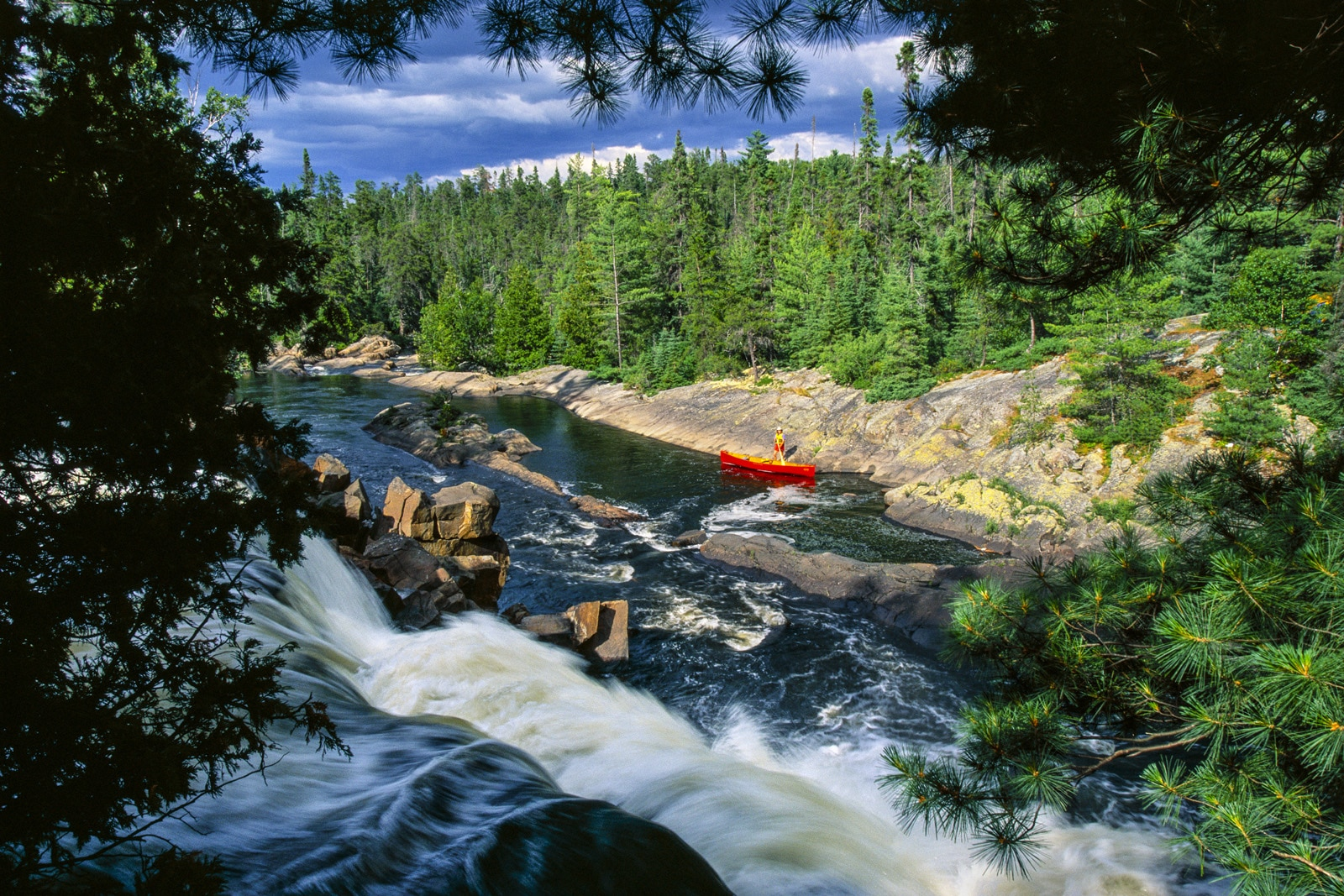 Canoer on shore of river with rapids