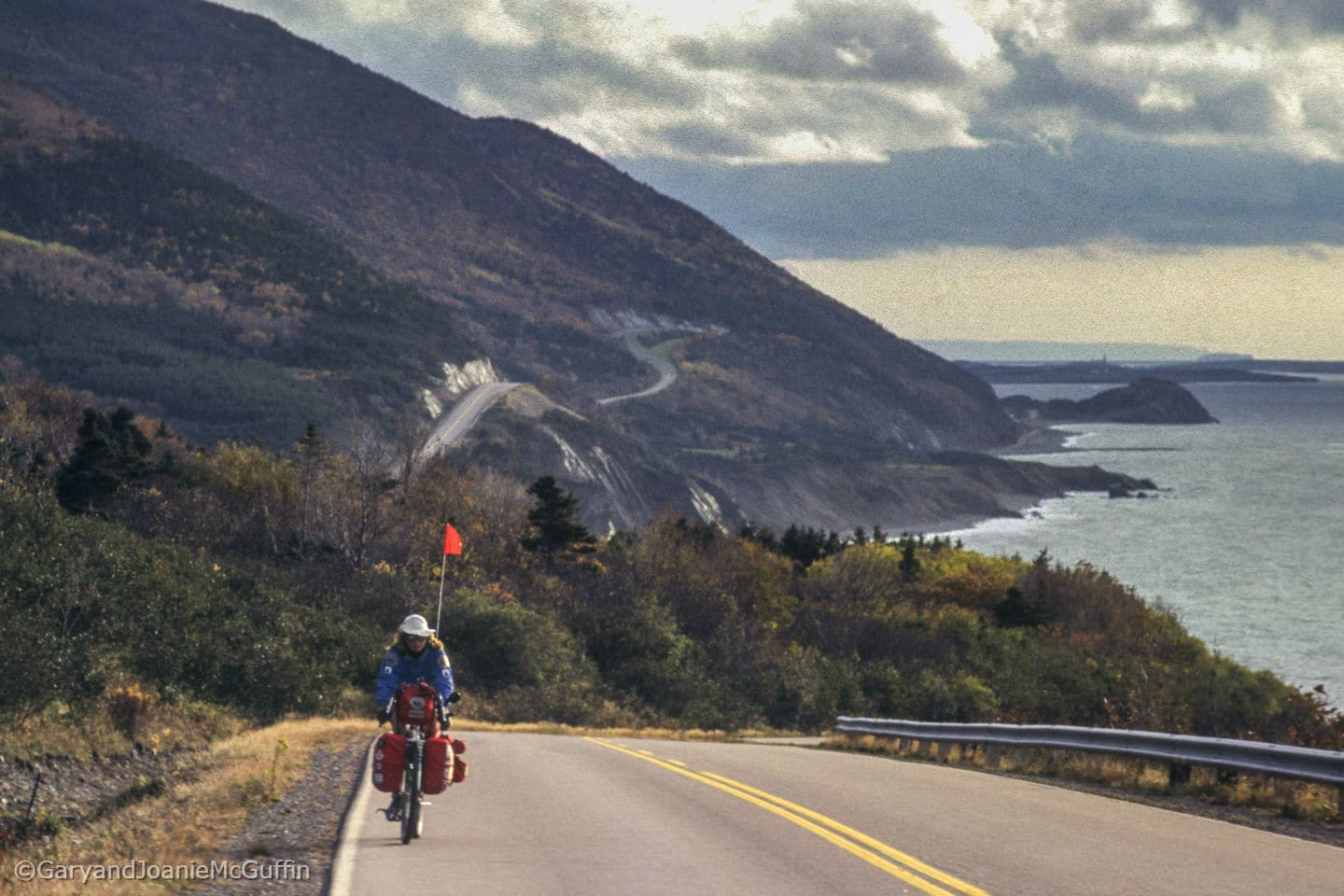 Biker on a highway with mountains and shore line in background