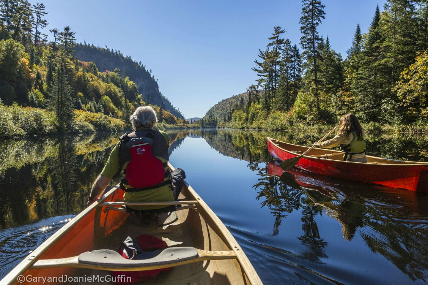 Two people canoeing on calm river in Northern Ontario
