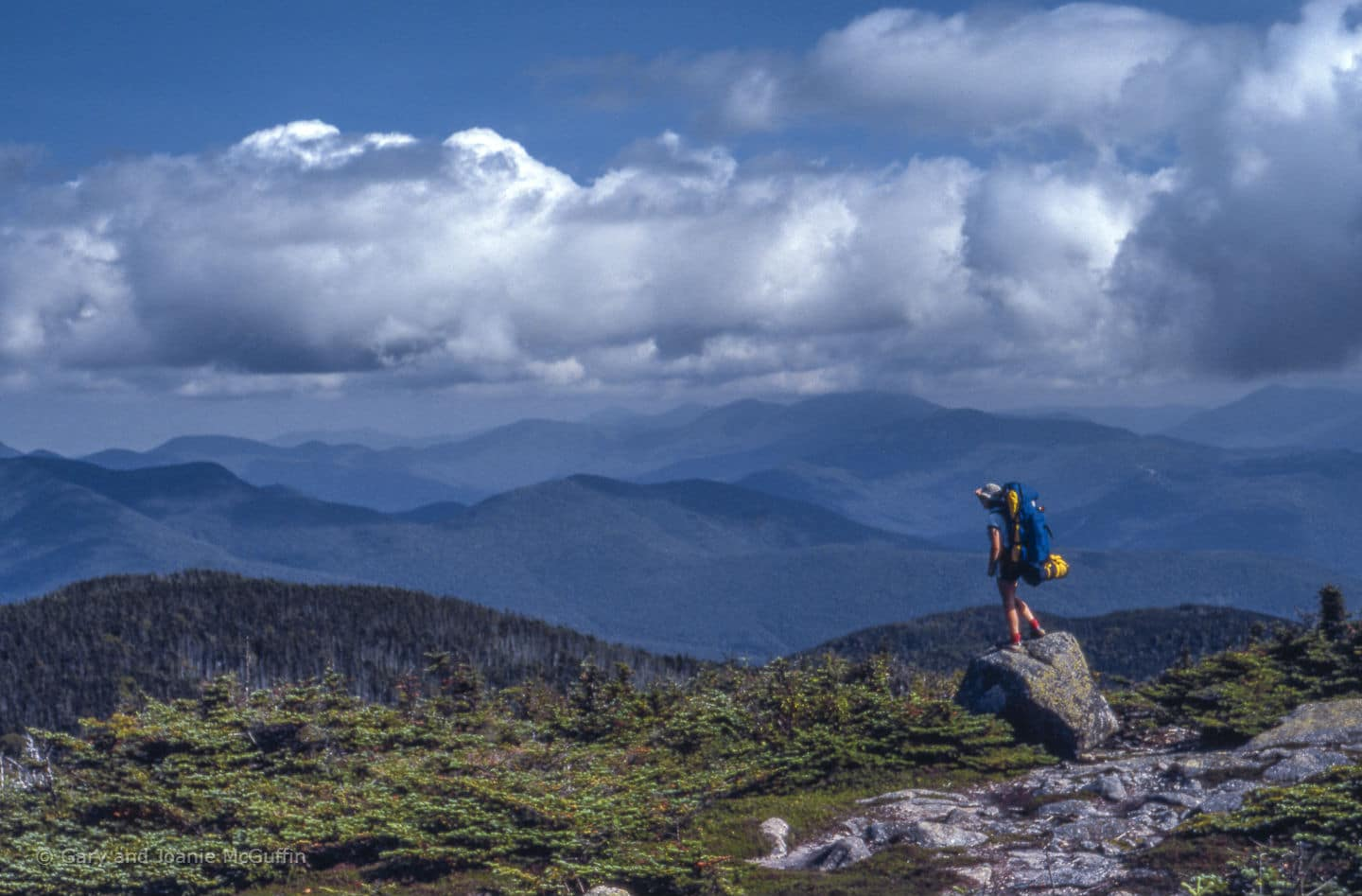 Hiker standing on a rock looking out on the mountains