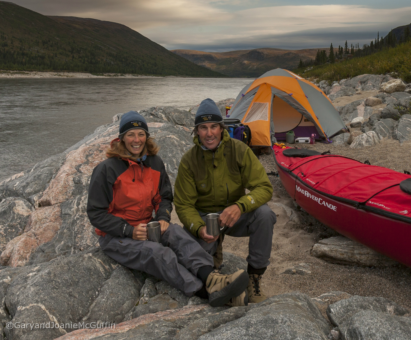 Couple sitting on rocks with their tent and canoe by a river