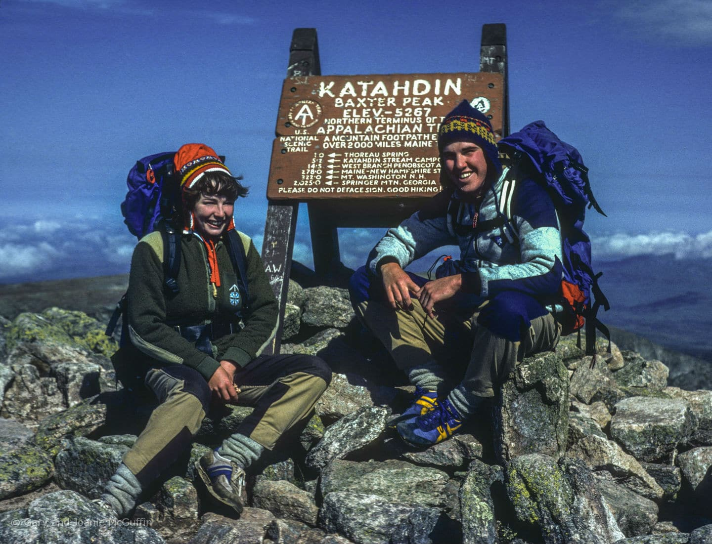 Two people sitting infront of Katahdin Baxter Peak sign on the Appalachian Trail