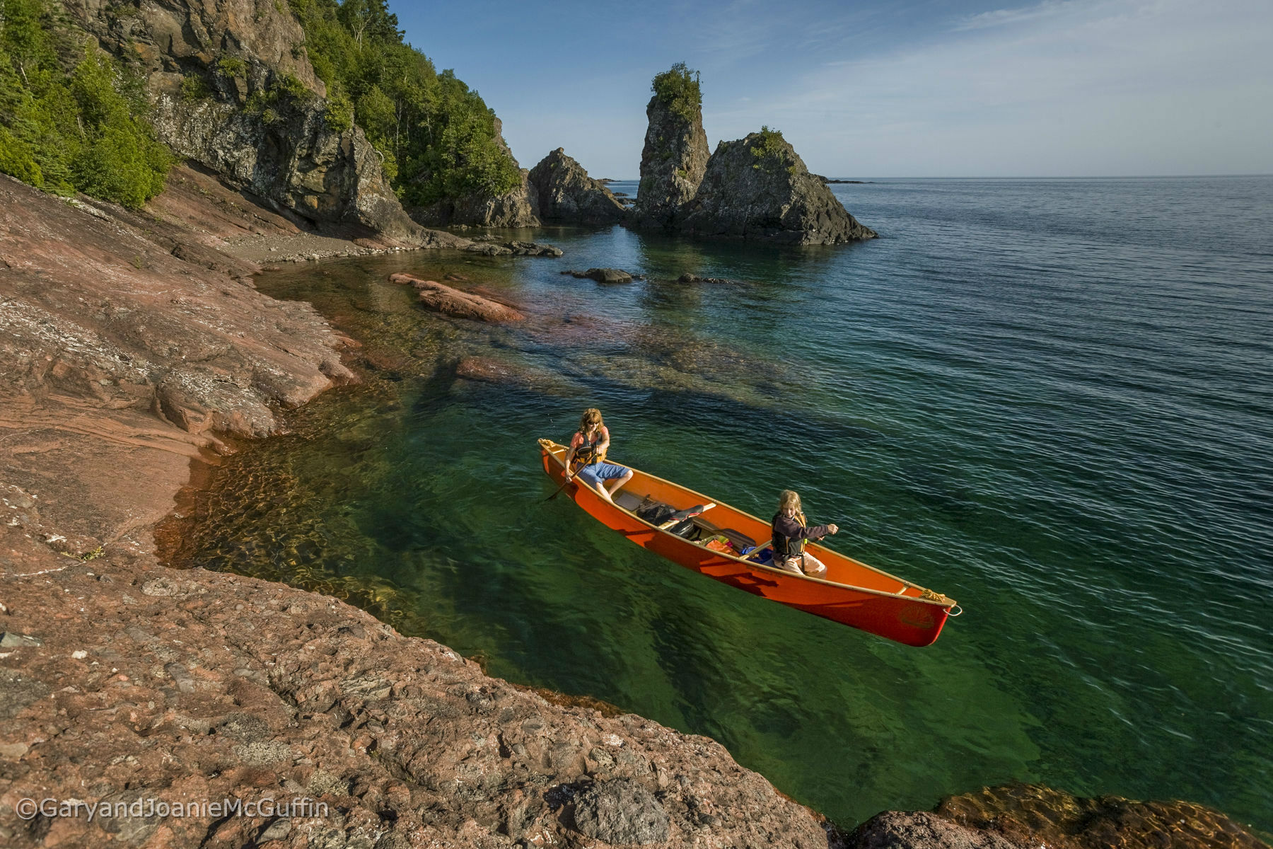 Two paddlers canoeing along shore line