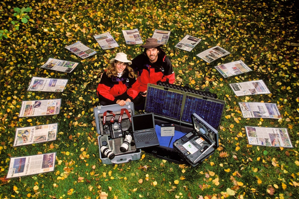 Outdoor adventure couple with equipment and newspaper articles